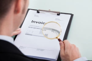 Cropped image of young businessman examining invoice through magnifying glass at office desk